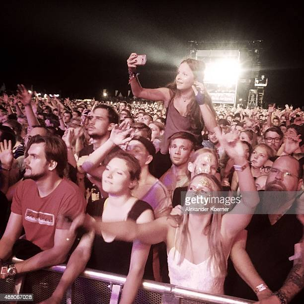 Fans cheer as the band Seeed performs during the second day of the Lollapalooza Berlin music festival at Tempelhof Airport on September 13, 2015 in...
