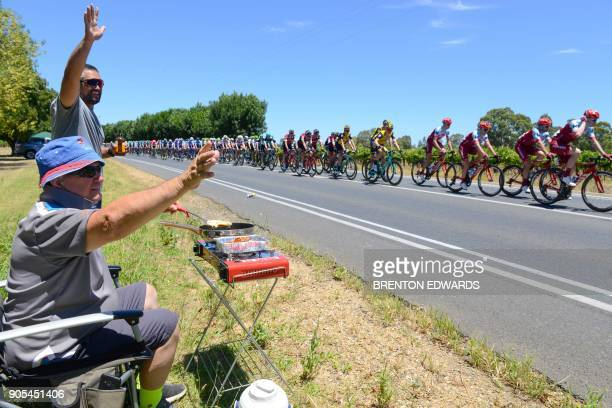 TOPSHOT Fans cheer as the peloton passes on the first day of the Tour Down Under cycling race in Adelaide on January 16 2018 / AFP PHOTO / BRENTON...