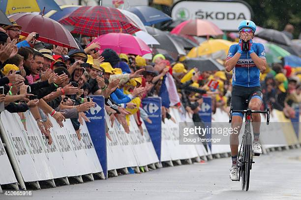 Fans cheer as they protect themselves from the rain as Ramunas Navardauskas of Lithuania and GarminSharp celebrates his victory in the nineteenth...