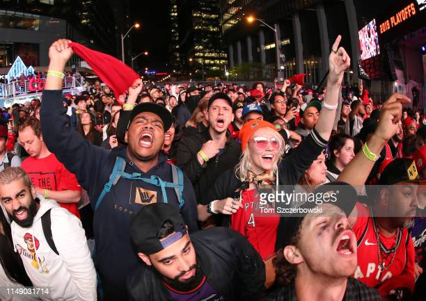 Fans cheer as they watch in the fourth quarter as they gather at Jurassic Park to watch the Golden State Warriors play against the Toronto Raptors...