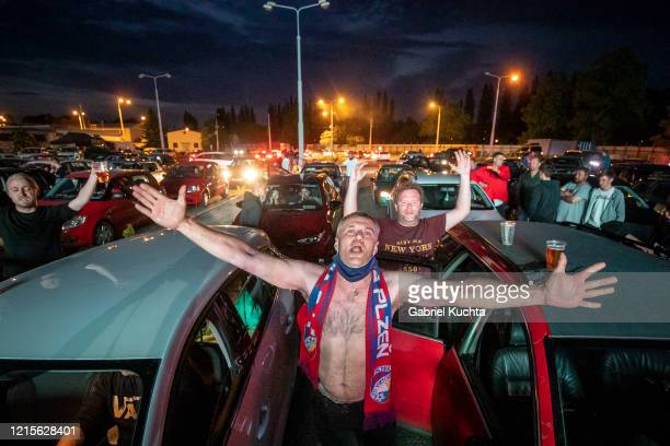 Fans cheer as they watch the Czech first division football match between FC Viktoria Plzen and AC Sparta Praha at a drivein movie theater on May 27...
