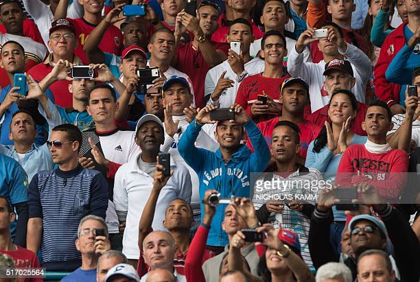 Fans cheer as US President Barack Obama and Cuban President Raul Castro arrive to attend a baseball game between the Tampa Bay Rays and the Cuban...