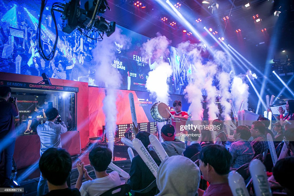 Fans cheer as Yang Jin Hyeob, left behind glass, wins the final round of the Electronic Arts Inc. (EA) Sports FIFA Online Championship at the Nexon Co. e-Sports Stadium in Seoul, South Korea, on Saturday, Oct. 17, 2015. Video game competitions, known as eSports, have been expanding as gamers seek to shift perceptions around their craft from a basement hobby to a serious money making industry. Photographer: Jean Chung/Bloomberg via Getty Images