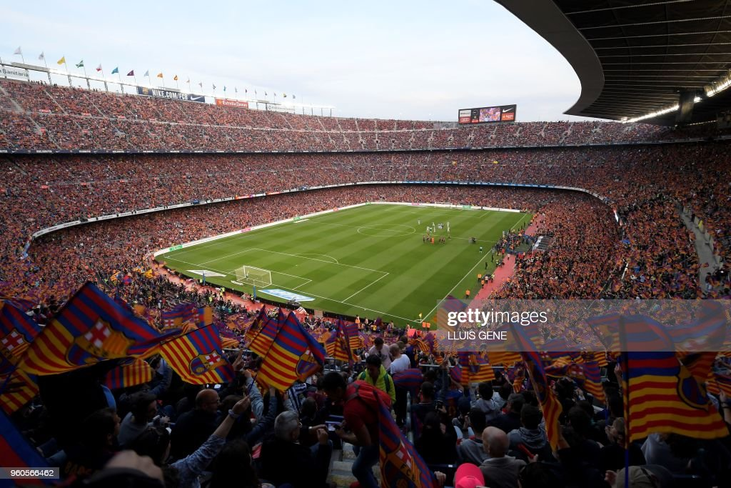 TOPSHOT - Fans cheer before the Spanish league football match between FC Barcelona and Real Sociedad at the Camp Nou stadium in Barcelona on May 20, 2018.