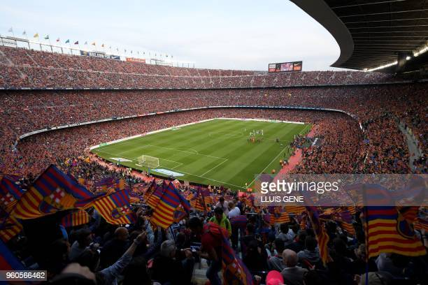 Fans cheer before the Spanish league football match between FC Barcelona and Real Sociedad at the Camp Nou stadium in Barcelona on May 20, 2018.
