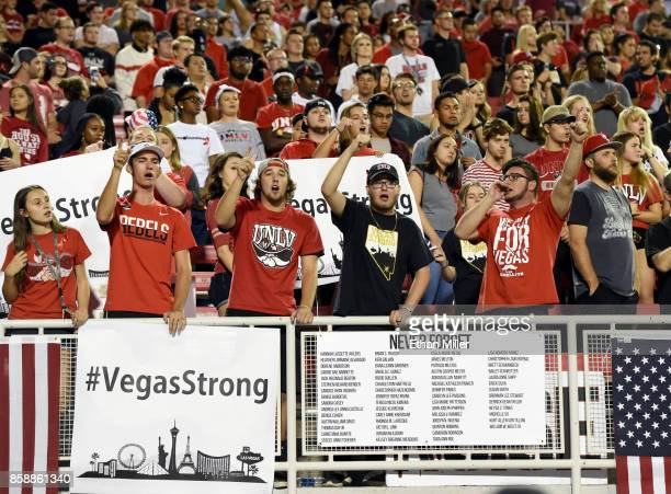 UNLV fans cheer behind a #VegasStrong sign and a sign listing the 58 victims killed in Sunday's mass shooting before the team's game against the San...