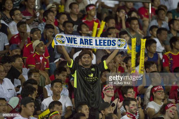 Fans cheer during the Leeds United FC and Myanmar National League All Star football match at Thuwana football staduim in Yangon on May 9 2018 Leeds...