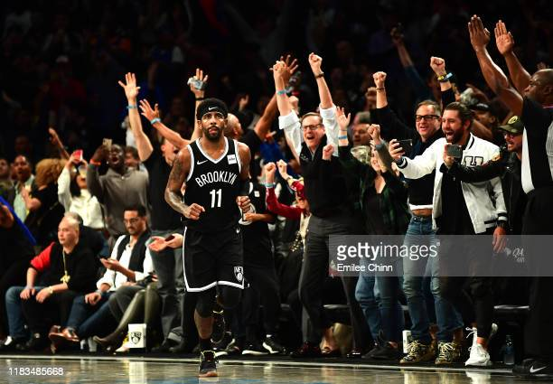 Fans cheer for Kyrie Irving of the Brooklyn Nets after he scores a three-pointer to put the Nets ahead in the second half of their game against the...