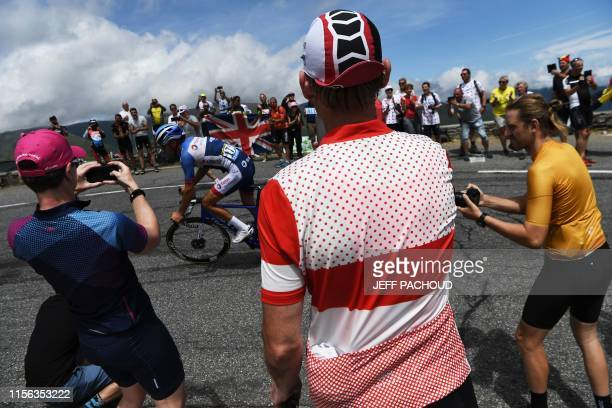 Fans cheer France's Lilian Calmejane in a curve uphill as he leads a breakaway during the twelfth stage of the 106th edition of the Tour de France...