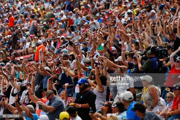 Fans cheer in the grandstand during the Monster Energy NASCAR Cup Series Pure Michigan 400 at Michigan International Speedway on August 13 2017 in...
