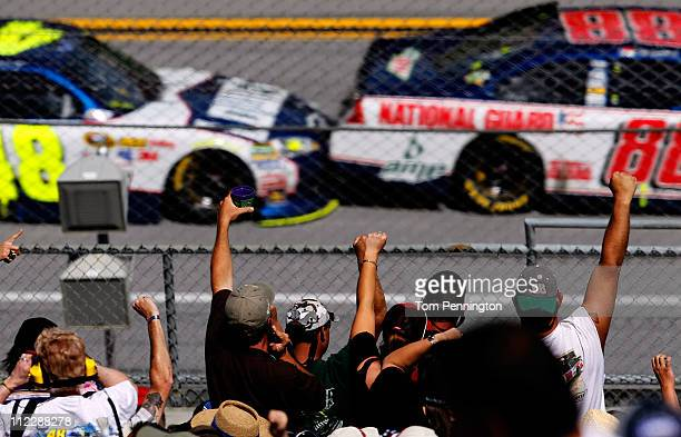 Fans cheer in the grandstands as Dale Earnhardt Jr driver of the National Guard/Amp Energy Chevrolet leads Jimmie Johnson driver of the Lowe's...