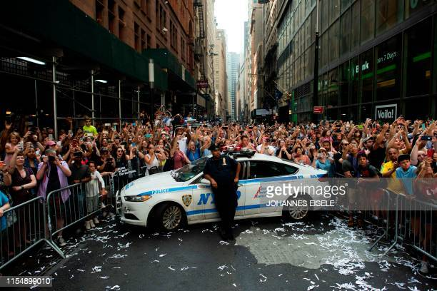 TOPSHOT Fans cheer on members of the World Cupwinning US women's team as they take part in a ticker tape parade for the women's World Cup champions...