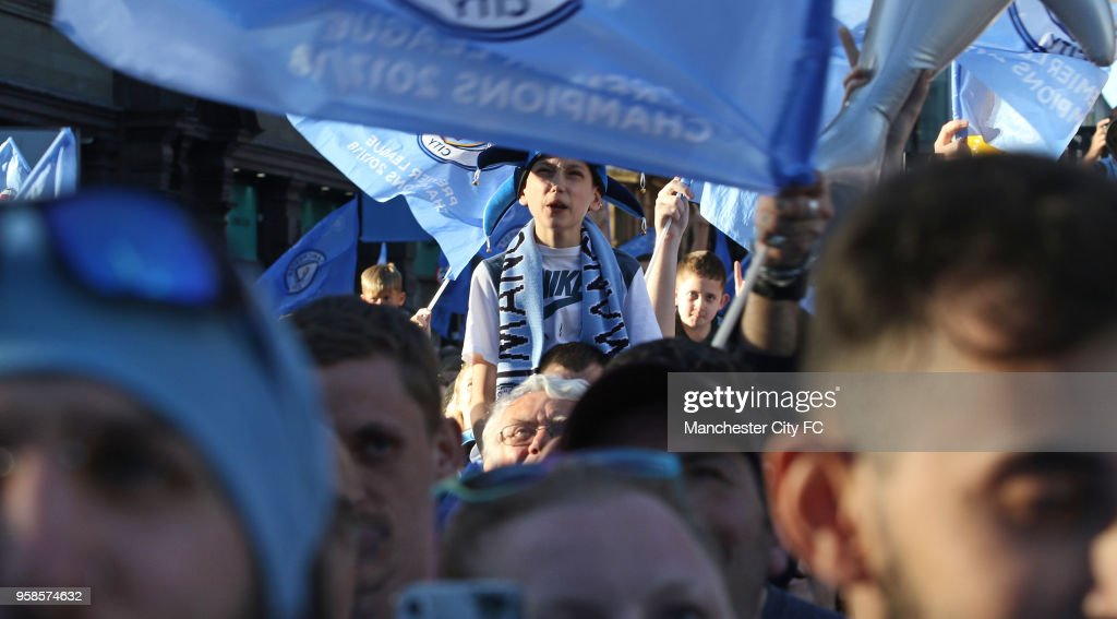 Fans cheer on players during a victory Parade by Manchester City FC on May 14, 2018 in Manchester, England.