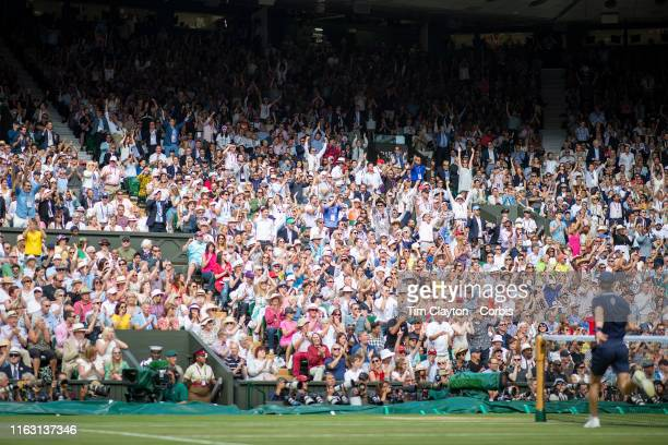 July 14: Fans cheer Roger Federer of Switzerland in action against Novak Djokovic of Serbia during the Men's Singles Final on Centre Court during the...