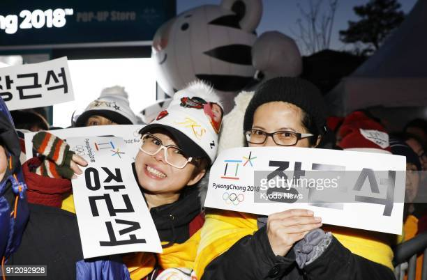 Fans cheer South Korean actor Jang Keun Suk holding signs bearing his name during the Pyeongchang Winter Olympic torch relay in Chuncheon South Korea...