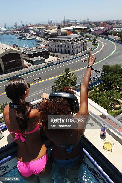 Fans cheer the field from a rooftop pool terrace as they get underway at the start of the European Grand Prix at the Valencia Street Circuit on June...