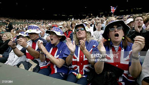 Fans cheer Tim Henman of Great Britain in action against Sebastien Grosjean of France during the men's quarter finals at the Wimbledon Tennis...