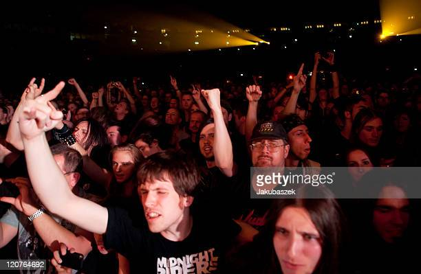 Fans cheer while the English Heavy Metal band Judas Priest performs live during a concert at the O2 World on August 9 2011 in Berlin Germany