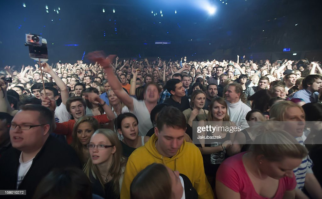 Fans cheer while the German reggae band Seeed performs live during a concert at the Max-Schmeling-Halle on December 8, 2012 in Berlin, Germany.