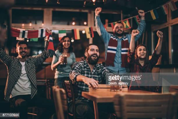 Fans cheering at the bar