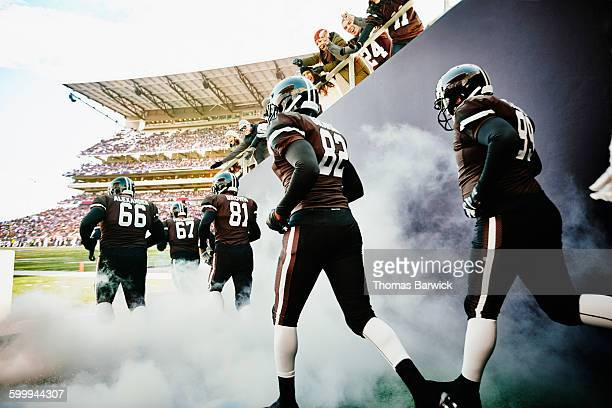 fans cheering football team running out of tunnel - sports event stock pictures, royalty-free photos & images