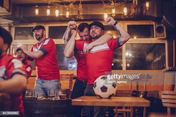 Fanáticos vitoreando en pub