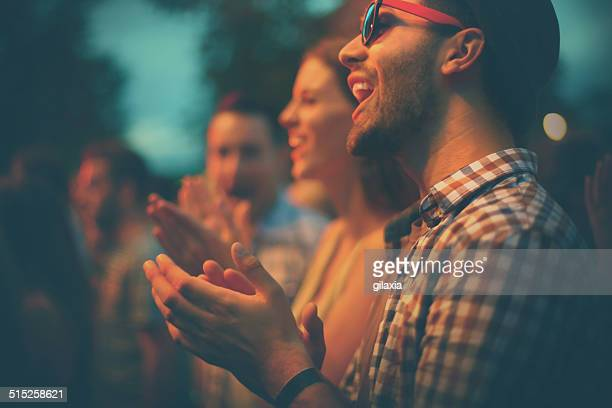 Fans clapping at concert.