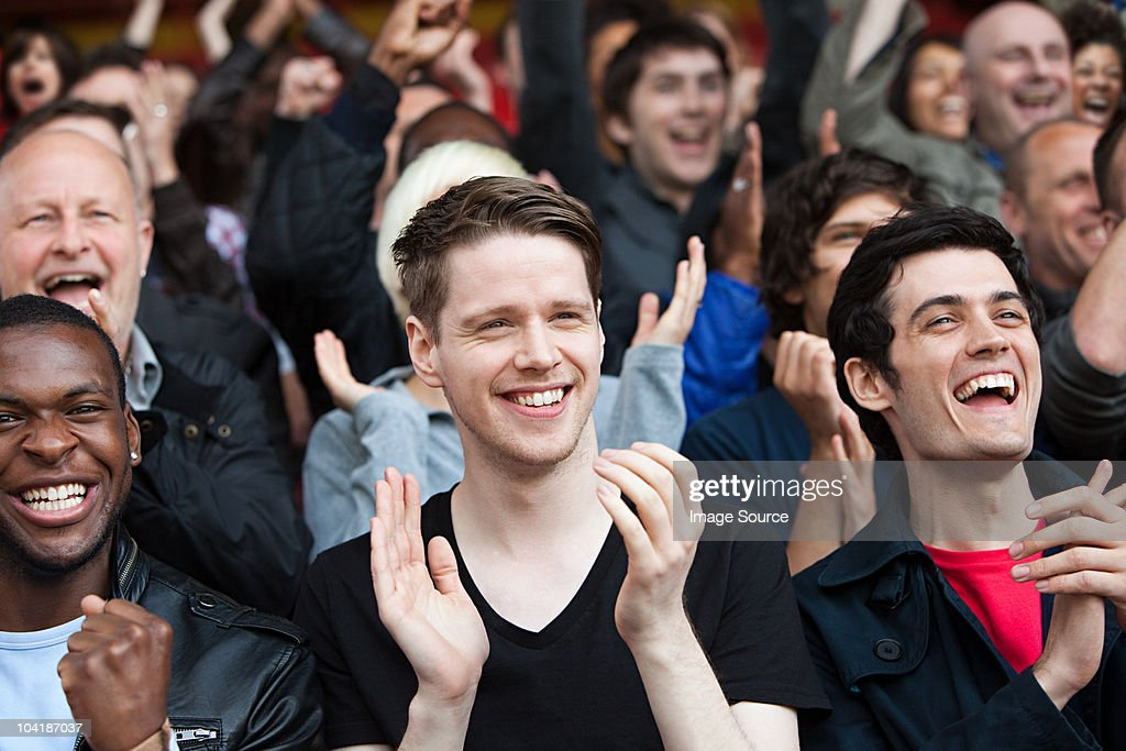 Fans clapping at football match : Stock Photo