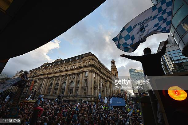 Fans climb on any available vantage point as Manchester City players parade the Barclays Premier League trophy in front of thousands of fans during...