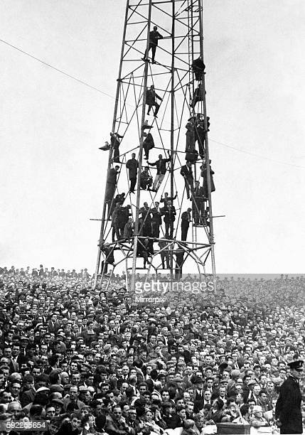 Fans climb the floodlight pylon to get a better view of the game 14th October 1961