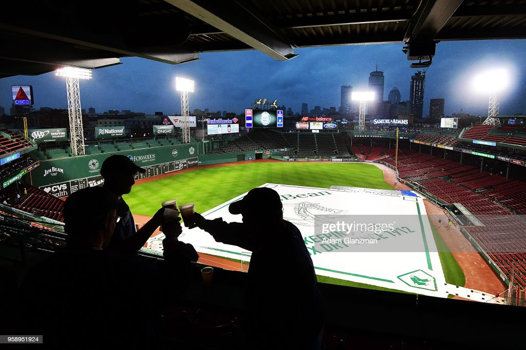 Fans clink their drinks as the game is delayed due to rain before a game between the Boston Red Sox and the Oakland Athletics at Fenway Park on May 15, 2018 in Boston, Massachusetts.