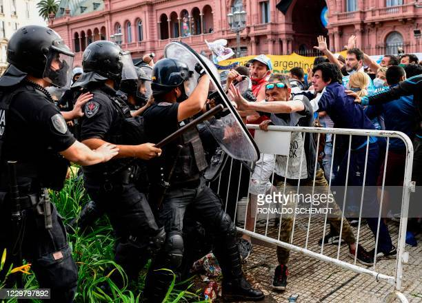 Fans confront riot police as they try to reach the Casa Rosada presidential palace to pay tribute to late Argentine football legend Diego Maradona in...