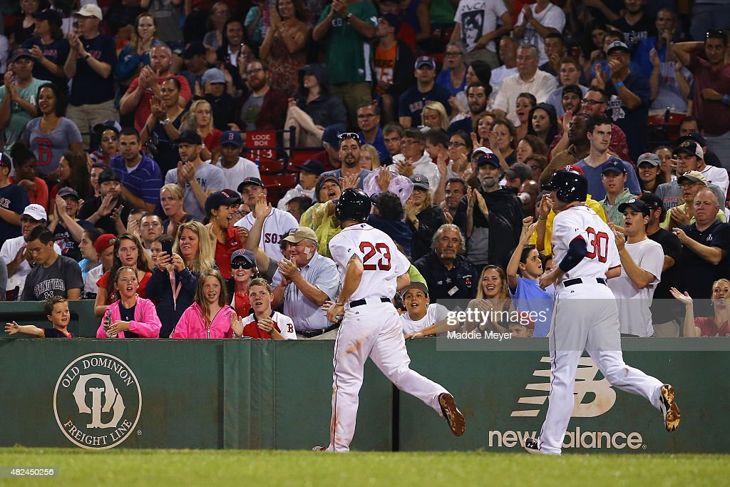 Fans congratulate Josh Rutledge #30 and Blake Swihart #23 of the Boston Red Sox after they scored runs against the Chicago White Sox during the sixth inning at Fenway Park on July 30, 2015 in Boston, Massachusetts.