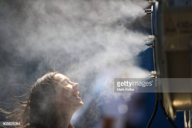 Fans cool down in front of a misting fan on day three of the 2018 Australian Open at Melbourne Park on January 17 2018 in Melbourne Australia
