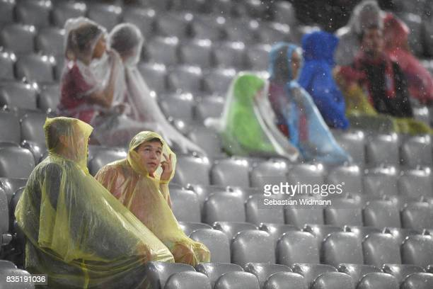 Fans cover themselves up in the stands during bad weather and rain during the Bundesliga match between FC Bayern Muenchen and Bayer 04 Leverkusen at...
