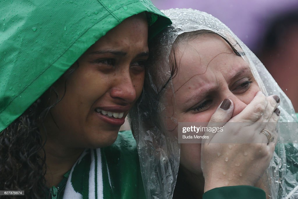Fans cry while paying tribute to the players of Brazilian team Chapecoense Real at the club's Arena Conda stadium in Chapeco, in the southern Brazilian state of Santa Catarina, on December 03, 2016. Players of the Chapecoense soccer team were among the 77 people on board the doomed flight that crashed into mountains in northwestern Colombia. Officials said just six people were thought to have survived, including three of the players. Chapecoense had risen from obscurity to make it to the Copa Sudamericana finals against Atletico Nacional of Colombia.