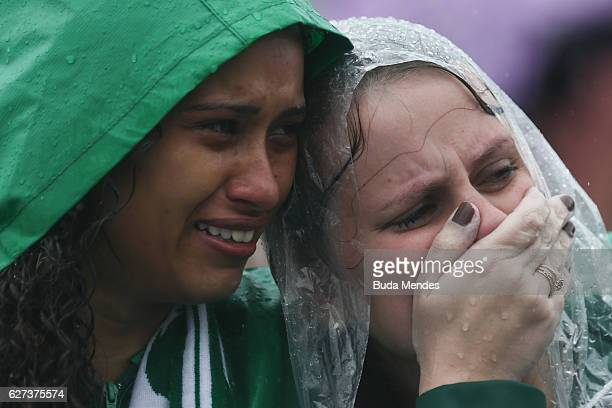 Fans cry while paying tribute to the players of Brazilian team Chapecoense Real at the club's Arena Conda stadium in Chapeco in the southern...