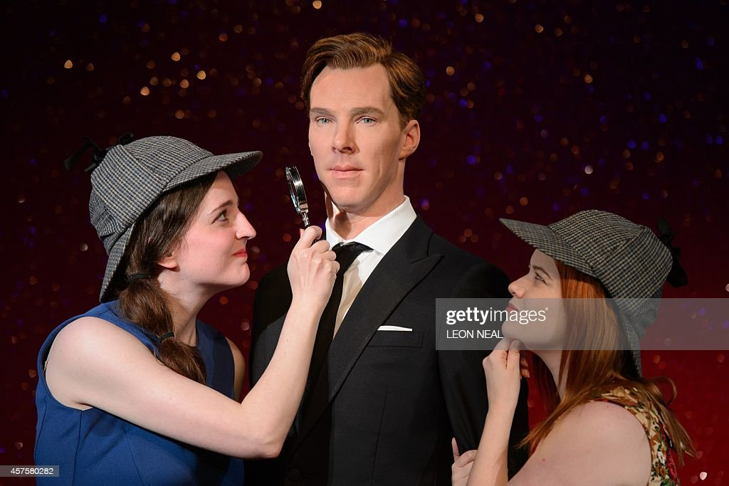 Fans Daisy England (L) and Charlie Mitchell (R) pose with Sherlock Holmes-style deerstalker hats and a magnifying glass around the new wax figure of British actor Benedict Cumberbatch as it is unveiled at Madame Tussauds in central London on October 21, 2014. Dressed in a dark suit the figure of Cumberbatch has been modelled to be 'premiere ready'.