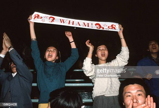 Fans dance in the aisle as they watch Wham including George Michael and Andrew Ridgeley playing a concert at Beijing's People's Stadium This was the...