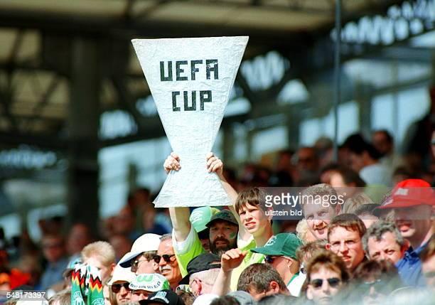 Fans des VfL Wolfsburg auf der Tribüne des VfLStadion einer hält einen selbstgebastelten UefaPokal hoch