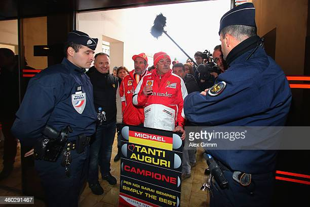 Fans discuss with police officers at the Grenoble University Hospital Centre where they mark the 45th birthday of former German Formula One driver...