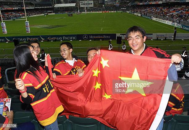 Fans display a Chinese flag as they watch a match between China and England during the Rugby Sevens at the Hong Kong Stadium 26 March 2004 Rugby...