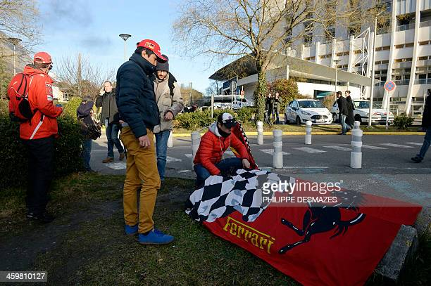 Fans display a Ferrari flag on December 30 2013 in front of the Grenoble University Hospital Centre in the French Alps where retired seventime German...