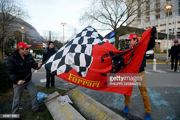 Fans display a Ferrari flag on December 31 2013 in front of the Grenoble University Hospital Centre French Alps where the retired seventime German...