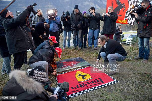 Fans display a Ferrari flag surrounded by journalists on December 31 2013 in front of the Grenoble University Hospital Centre in the French Alps...
