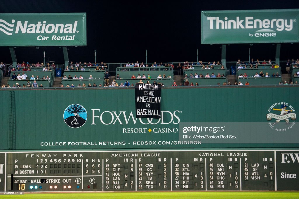 Fans display a sign that reads 'Racism is as American as Baseball' over the Green Monster during the fourth inning of a game between the Boston Red Sox and the Oakland Athletics on September 13, 2017 at Fenway Park in Boston, Massachusetts.