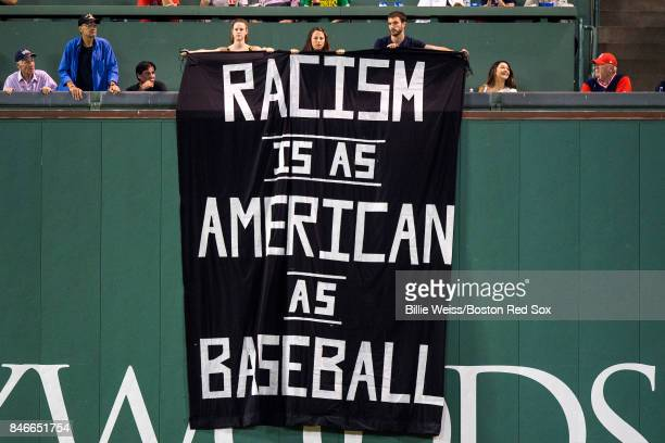 Fans display a sign that reads 'Racism is as American as Baseball' over the Green Monster during the fourth inning of a game between the Boston Red...