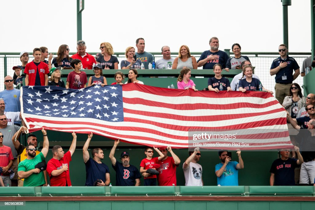 Fans display an American flag on top of the Green Monster as God Bless America is sung during a game between the Boston Red Sox and the Seattle Mariners on June 24, 2018 at Fenway Park in Boston, Massachusetts.