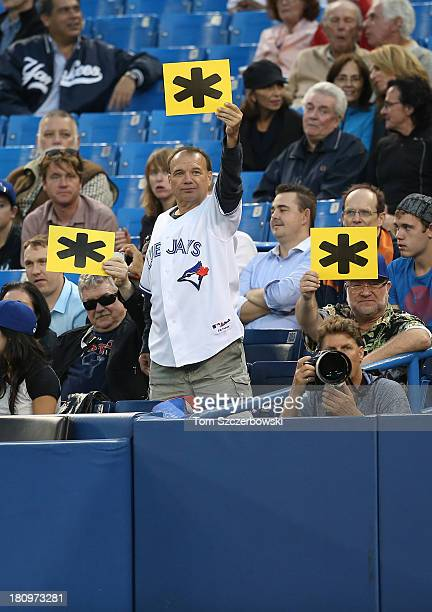Fans display asterisk placards at Alex Rodriguez of the New York Yankees during his at bat in the first inning during MLB game action against the...