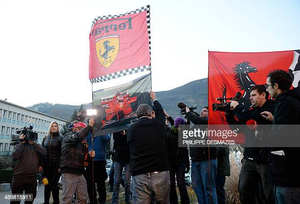Fans display Ferrari flags as they gather outside the Grenoble University Hospital Centre in the French Alps where retired seventime German Formula...